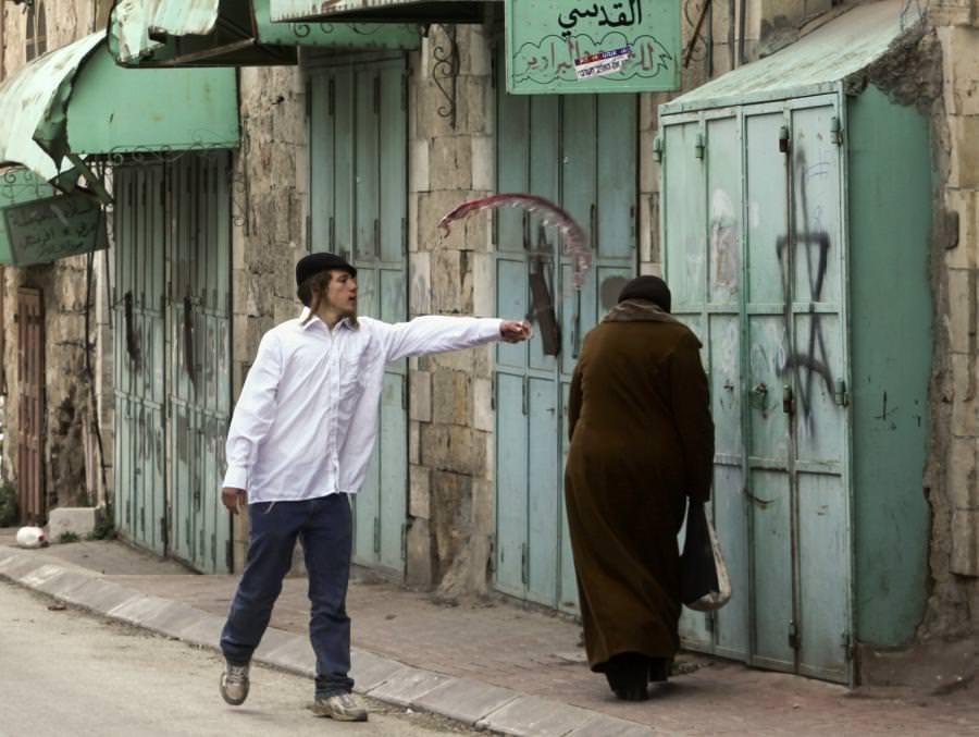 مستوطن متطرف يرشق امرآة فلسطينية بالخمر