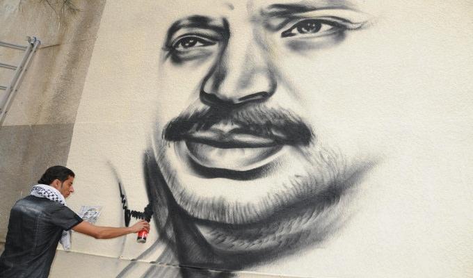 الفنان الفلسطيني محمد الديري يرسم صور للشهيد ياسر عرفات في مخيم البداوي